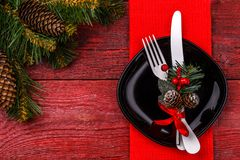 Christmas table place setting with red napkin, black plate, white fork and knife, decorated sprig of mistletoe and. Christmas pine branches. New Year Clock Stock Image