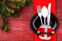 Christmas table place setting with red napkin, black plate, white fork, spoon and knife, decorated Santa jacket and Royalty Free Stock Image
