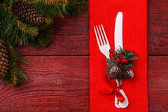 Christmas table place setting with red napkin, white fork and knife, decorated sprig of mistletoe and christmas pine. Branches. Christmas holidays background Royalty Free Stock Photos