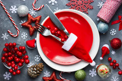 Christmas table place setting with red plate, cutlery in santa h Royalty Free Stock Photo