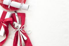 Christmas Table Place Setting in Red, White and Silver with Silverware, a gift, and party cracker on White Cloth Background with r. Oom or space for copy, text stock photo