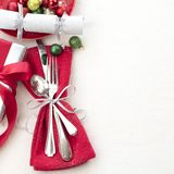 Christmas Table Place Setting in Red, White and Silver with Silverware, a gift, and party cracker on White Cloth Background with r