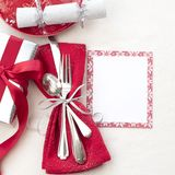 Christmas Table Place Setting in Red, White and Silver with Silverware, a gift, and party cracker on White Cloth Background with r. Oom or space for copy, text royalty free stock photo