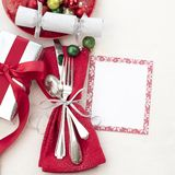 Christmas Table Place Setting in Red, White and Silver with Silverware, a gift, and party cracker on White Cloth Background with r. Oom or space for copy, text stock photography