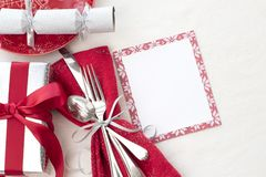 Christmas Table Place Setting in Red, White and Silver with Silverware, a gift, and party cracker on White Cloth Background with r. Oom or space for copy, text stock images