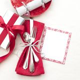 Christmas Table Place Setting in Red, White and Silver with Silverware, a gift, and party cracker on White Cloth Background with r. Oom or space for copy, text royalty free stock photography