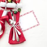 Christmas Table Place Setting in Red, White and Silver with Silverware, a gift, and party cracker on White Cloth Background with r. Oom or space for copy, text royalty free stock photos