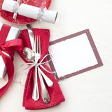 Christmas Table Place Setting in Red, White and Silver with Silverware, a gift, and party cracker on White Cloth Background with r. Oom or space for copy, text stock image