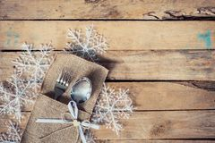 Christmas table place setting and silverware, snowflakes on wood. En background with space Royalty Free Stock Photography