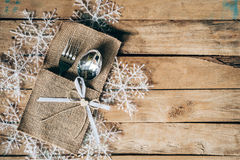 Christmas table place setting and silverware, snowflakes on wood. En background with space Royalty Free Stock Photo