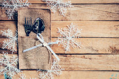 Christmas table place setting and silverware, snowflakes on wood. En background with space Royalty Free Stock Images