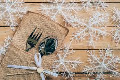 Christmas table place setting and silverware, snowflakes on wood. En background with space Royalty Free Stock Photos