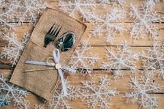Christmas table place setting and silverware, snowflakes on wood. En background with space Stock Photo
