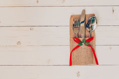 Christmas table place setting and silverware on wood with space Royalty Free Stock Image