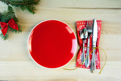 Christmas table with plate, cutlery on a napkin, a sprig of fir with toys. Christmas background: oaks table, plate and cutlery on a napkin, a sprig of fir with Stock Photo