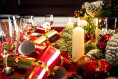 Christmas table set for lunch. A christmas dining table ready for christmas lunch with place settings, crackers, decorations and candles stock photography