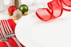 Christmas Table Setting. Holiday ornaments decorate a restaurant table setting in festive red and green Christmas colors with copy space on an empty white plate Stock Photography