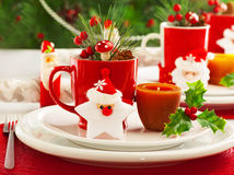 Christmas table setting. Picture of beautiful Christmas table setting, shining white plate with red cup for coffee decorated holiday dinner, branch of berry and stock image