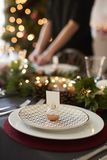Christmas table setting with bauble name card holder arranged on a plate and green and red table decorations stock photos