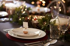 Christmas table setting with bauble name card holder arranged on a plate and green and red table decorations stock image