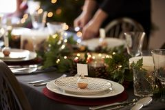 Christmas table setting with bauble name card holder arranged on a plate and green and red table decorations royalty free stock images