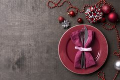 Christmas table setting with red festive decor and fork and knife on wood table. Top view. Xmas Party royalty free stock image