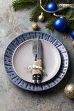 Christmas table setting on decor background. Blue and gray plate, cutlery, festive decorations stock photo