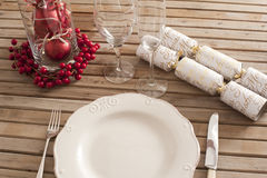 Christmas Table setting with decorations. Festive table setting of white plate, cutlery, vine glasses with red berries decorations and wrapped candies over Royalty Free Stock Photo