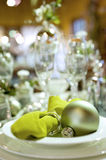 Christmas table setting detail. Closeup detail of a modern table setting for Christmas or other festive parties around this season. Green dishes decorated with Stock Photography