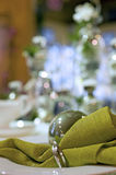Christmas table setting detail. Closeup detail of a modern table setting for Christmas or other festive parties around this season. Green dishes decorated with Stock Image