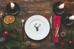 Christmas table setting with empty plate, candles, textile. Christmas table setting with empty plate, silverware, burning candles, red table textile on rustic royalty free stock photos