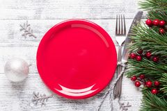 Christmas table setting with empty red plate, gift box and silverware on light wood background. Fir tree branch, holly berries. royalty free stock photography
