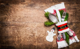 Christmas table setting with festive decor, napkin, cutlery and snowman on rustic wooden background , top view Royalty Free Stock Image