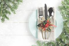 Christmas table setting with fir branches and snow on white wooden table. Xmas background with dishware. Top view with copy space Stock Photos