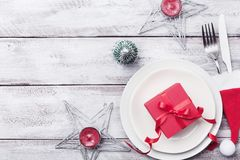 Christmas table setting. Gift box, fir tree, white plate and silverware on rustic table top view. Preparation for holiday dinner. Royalty Free Stock Images