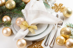 Christmas table setting in gold tones. Festive Christmas table setting, table decorations in gold tones, with fir branches, baubles, decorations royalty free stock photos