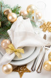 Christmas table setting in gold tones. Festive Christmas table setting, table decorations in gold tones, with fir branches, baubles, decorations stock photos