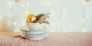 Christmas table setting. Not served white dishes with gold decor and fir-tree on beige tablecloth with blurred lights on the wall. Festive background. Wide royalty free stock photography