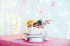 Christmas table setting. Not served white dishes with gold decor and fir-tree on pink tablecloth with blurred lights and new year. Balls on wall. Festive stock image