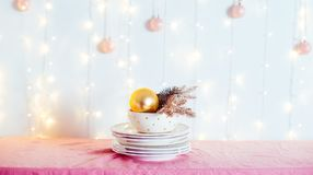 Christmas table setting. Not served white dishes with gold decor and fir-tree on pink tablecloth with blurred lights on the wall. Festive background. Wide royalty free stock image