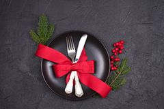 Christmas table setting with plate, cutlery, red ribbon and berries. Winter holidays and festive background Stock Photo