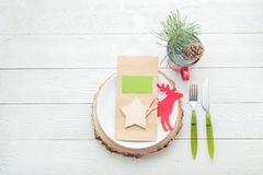 Christmas table setting with plate, fork, knife, menu card, some Christmas decor. On wooden background Royalty Free Stock Photography