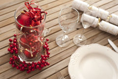 Christmas table setting with red decorations. And berries on a slatted wood table ready to celebrate the holiday season Royalty Free Stock Photography