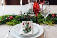 Christmas table setting. With red glasses and green twigs royalty free stock photo