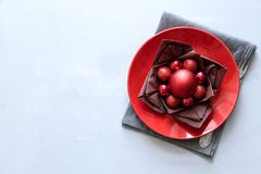 Christmas table setting with red plate, brown napkin in lotus shape and balls on gray wooden background. Holiday decorations. Concept. Flat lay. Top view. Copy stock images