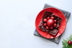 Christmas table setting with red plate, brown napkin in lotus shape and balls on gray wooden background. Holiday decorations. Concept. Flat lay. Top view. Copy stock photos
