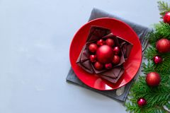 Christmas table setting with red plate, brown napkin in lotus shape and balls on gray wooden background. Holiday decorations. Concept. Flat lay. Top view. Copy royalty free stock image