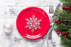 Christmas table setting with red plate, gift box and silverware on light wood background. Fir tree branch. stock image