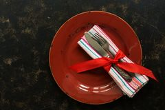 Christmas table setting , red plate, vintage cutlery and napkin tied with a ribbon on a dark rustic background.Top view, flat lay