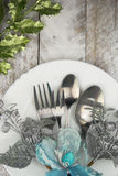 Christmas table setting in silver and green tone on wooden table Royalty Free Stock Photo